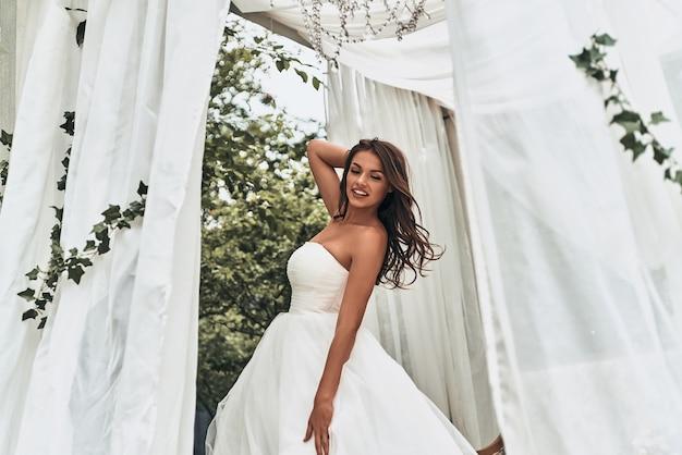 Sensuele bruid. aantrekkelijke jonge vrouw in trouwjurk die de hand achter het hoofd houdt en glimlacht terwijl ze buiten staat