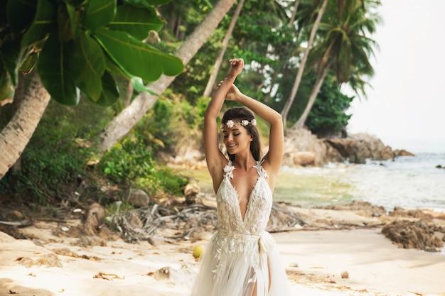 Sensuele bruid die mooie huwelijkskleding op het tropische eiland draagt
