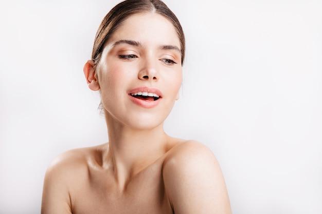 Sensuele donkerblonde dame zonder make-up vormt voor portret zonder filters op witte muur.