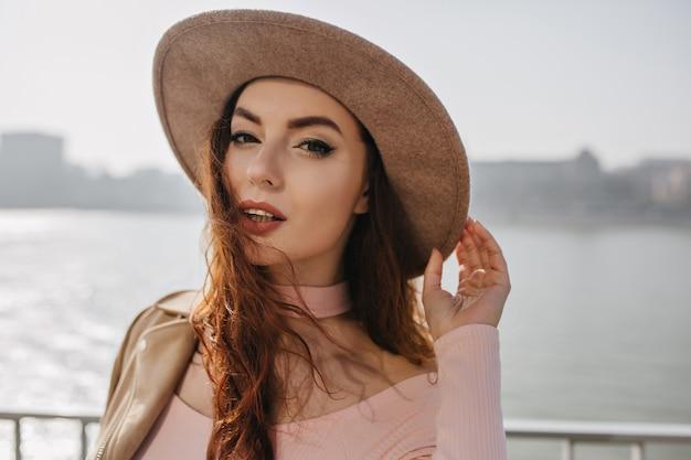 Sensuele donkerharige vrouw die haar hoed aanraakt en met belangstelling op de riviermuur kijkt