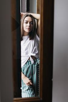 Sensuele donkerharige vrouw met geïnteresseerde gezichtsuitdrukking die thuis stelt. binnen schot van knap donkerbruin meisje in wit overhemd en groene broek.