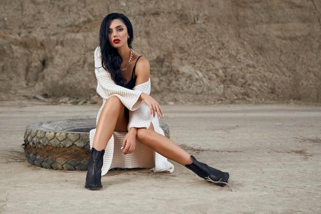 Sensuele jonge brunette in zwarte bodywear en gebreid vest zittend op oude grote band onder woestijn