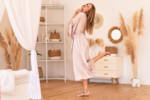 Sensuele jonge mooie blonde vrouw die zich voordeed in een modern trendy boho-interieur in luxe zijden kimono