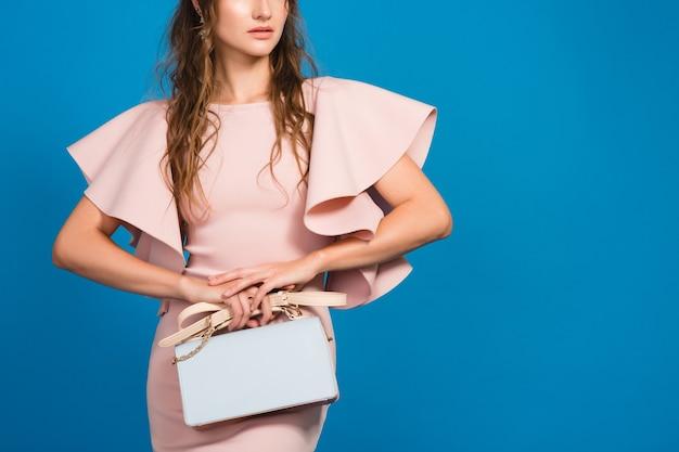 Sensuele jonge stijlvolle sexy vrouw in roze luxe jurk, zomer modetrend, chique stijl, blauwe studio achtergrond, trendy handtas te houden
