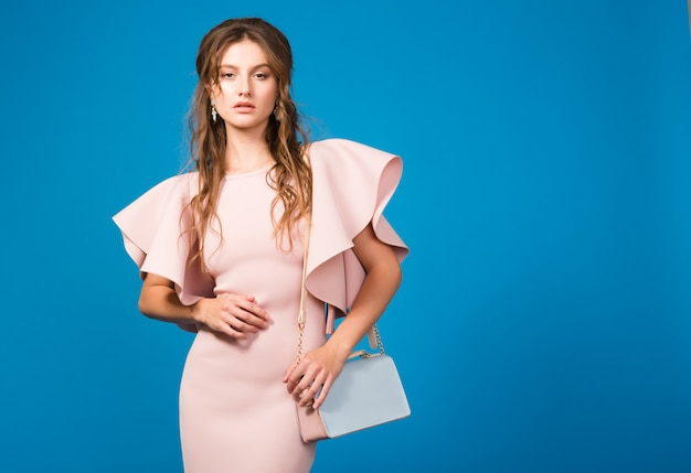 Sensuele jonge stijlvolle sexy vrouw in roze luxe jurk, zomer modetrend, chique stijl, trendy handtas te houden