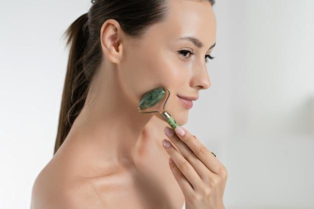 Sensuele jonge vrouw die gezicht met jaderol masseert over witte studioachtergrond. kaukasisch model dat zorgt voor natuurlijke schoonheid. schoonheidsroutine en huidprocedures concept.