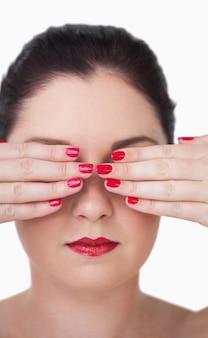 Sensuele jonge vrouw die ogen behandelt met rode geschilderde vingerspijkers tegen witte achtergrond