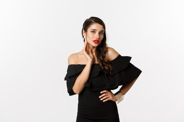 Sensuele jonge vrouw in zwarte kleding, die haar oorringen toont en sexy camera bekijkt, die zich over witte achtergrond bevindt.