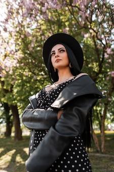 Sensuele jonge vrouw in zwarte vintage jurk in mooie stijlvolle hoed in trendy leren jas staat in het park op de achtergrond van lila bomen. mooie sexy meisje in elegante slijtage in zonnige dag in de natuur. kunnen.
