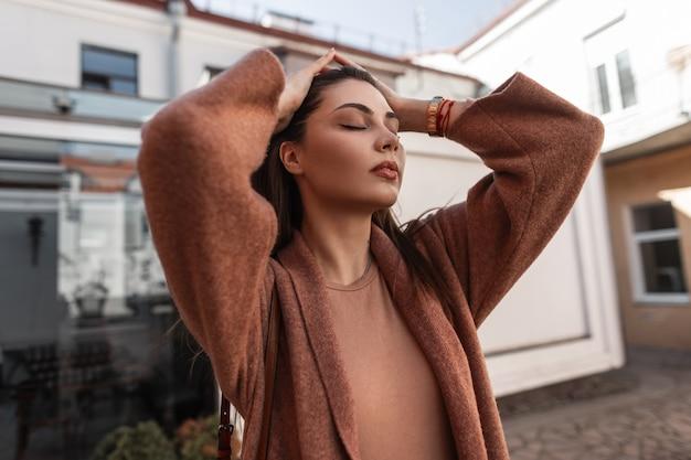 Sensuele jonge vrouw met gesloten ogen met sexy lippen in stijlvolle kleding maakt luxe lang haar recht. vrouwelijk portret mooi meisje in jas in beige elegant shirt op straat in de stad op lentedag.