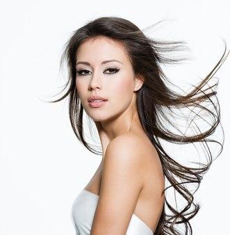 Sensuele jonge vrouw met mooie lange bruine haren, poseren geïsoleerd op wit