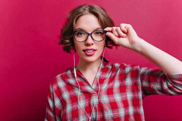 Sensuele jonge vrouw met roze lippen die met belangstelling kijken en glazen aanraken. charmant krullend meisje met tatoeage poseren in witte oortelefoons.