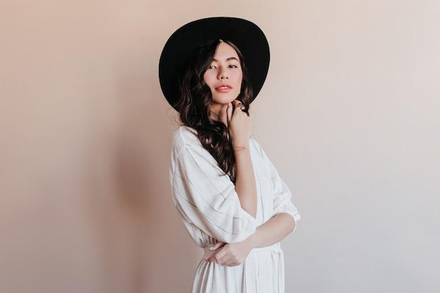 Sensuele koreaanse vrouw die in zwarte hoed camera bekijkt. studio shot van extatisch aziatisch model geïsoleerd op beige achtergrond.