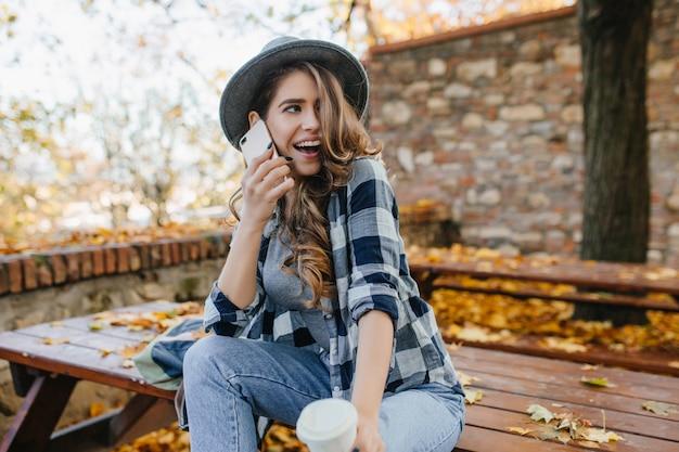 Sensuele krullende vrouw in hoed grappige emoties uitdrukken tijdens fotoshoot in herfst tuin