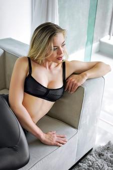 Sensuele mooie blonde vrouw die zich voordeed op de bank, sportief en gezond.