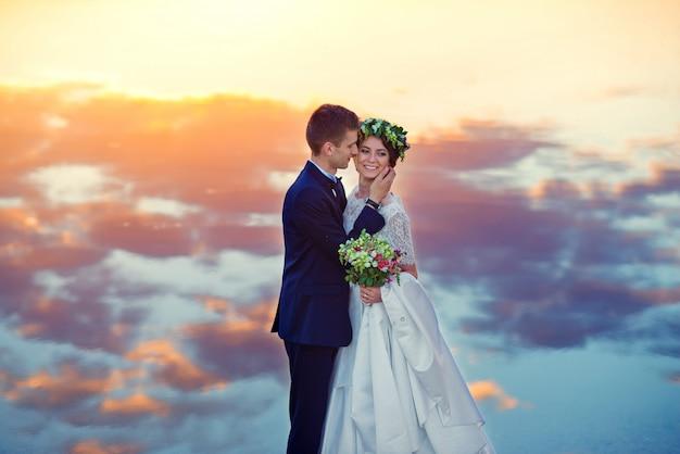 Sensuele mooie bruid en knappe bruidegom teder knuffelen