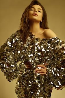 Sensuele mooie brunette vrouw in een glanzende mode-jurk van pailletten