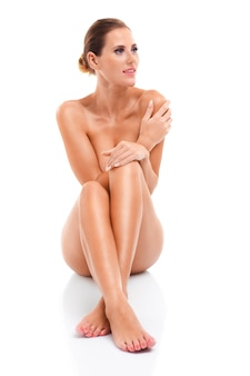 Sensuele naakte vrouw zittend op een witte achtergrond