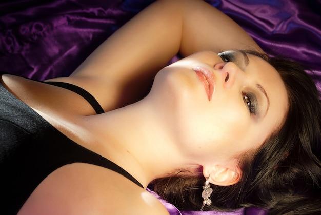 Sensuele schoonheid vrouw portret op paarse zijde bed