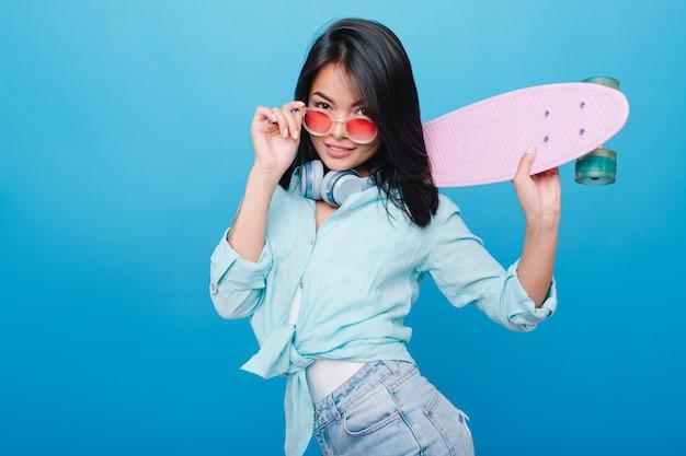 Sensuele spaanse vrouw die in katoenen blauw overhemd roze zonnebril en longboard houdt. indoor portret van een prachtig latijns vrouwelijk model in jeans ontspannen