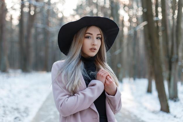 Sensuele stijlvolle mooie jonge vrouw in een gebreide vintage jurk in een stijlvolle zwarte hoed in een elegante roze jas poseren.