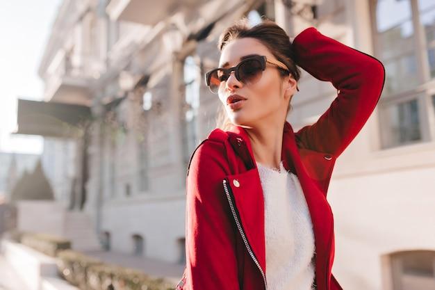 Sensuele vrouw in grote zonnebril spelen met haar haren in zonnige dag