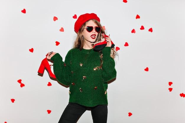 Sensuele vrouw in het elegante baret stellen met rode hoge hakschoenen in handen