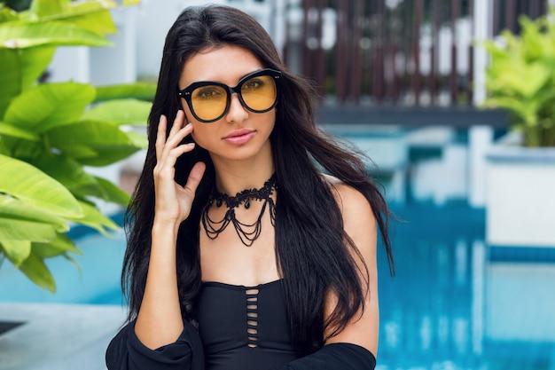 Sensuele vrouw in trendy ketting en zwarte badmode bij het zwembad