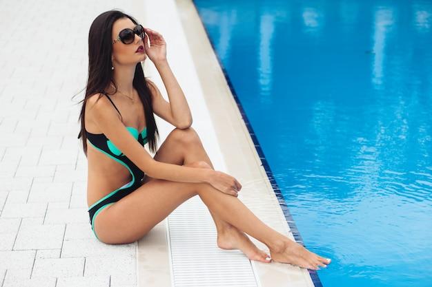 Sensuele vrouw in zwempak het ontspannen bij tropische toevlucht
