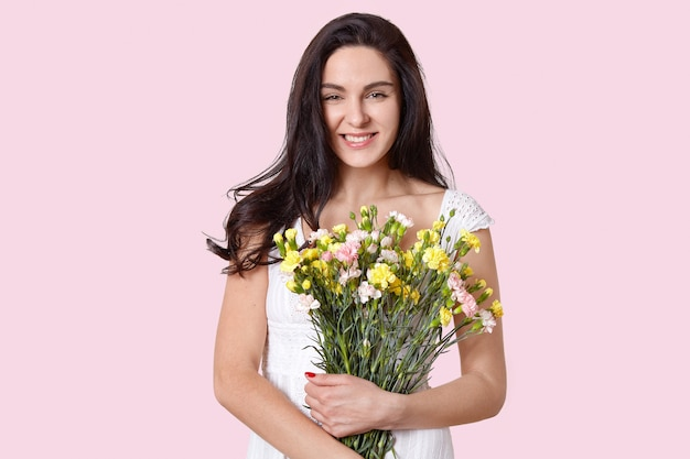 Sensuele vrouw met brede glimlach, houdt bloemen dicht