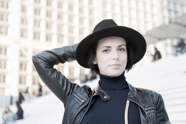 Sensuele vrouw met donkerbruin haar, kapsel. vrouw in zwarte hoed pose op trappen in parijs, frankrijk, mode. schoonheid, uiterlijk, make-up. mode, accessoire, stijl. huidverzorging, jeugd, gezicht.