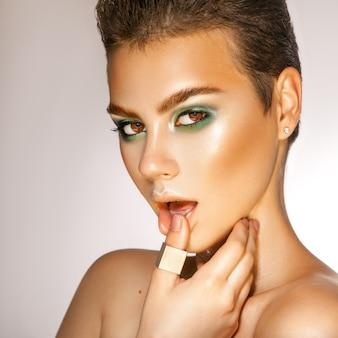 Sensuele vrouw met groene kleuren make-up in studio kijken camera grijze achtergrond verleiding
