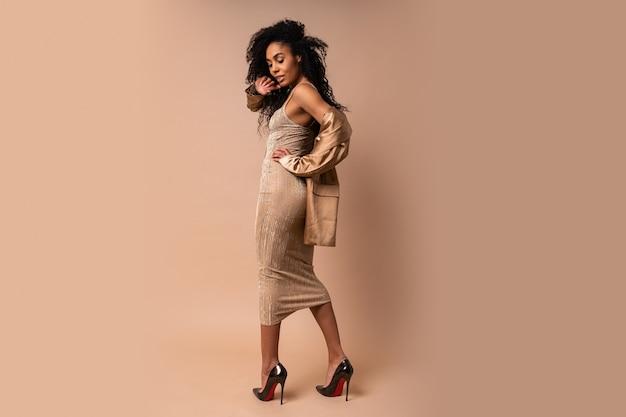 Sensuele vrouw met volumineus krullend kapsel in het elegante feestoutfit poseren