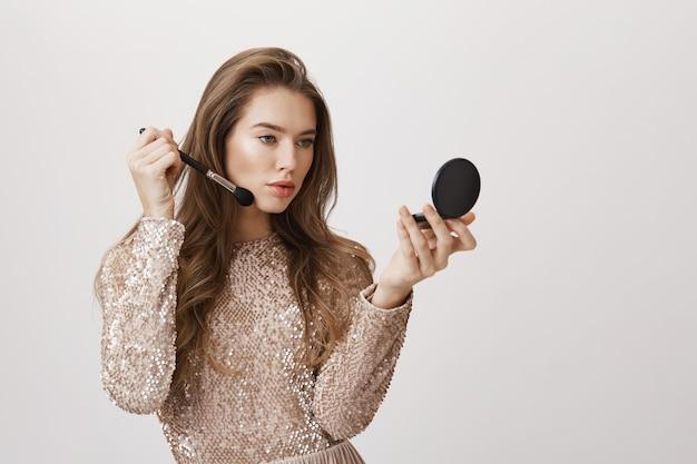 Sensuele vrouwelijke spiegel past make-up toe