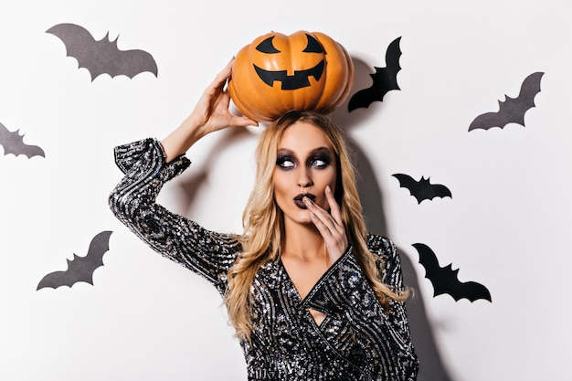Sensuele vrouwelijke tovenaar die speels in halloween stelt. binnen schot van mooie blonde vampier.