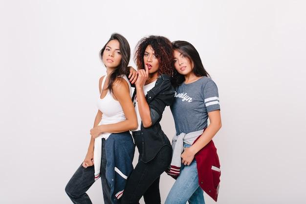 Sensuele zwarte vrouw in skinny jeans poseren zachtjes aanraken van latijns-vriendin. indoor portret van mooi aziatisch meisje in grijs t-shirt staande naast universiteitsgenoten.