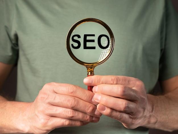 Seo acroniem woord in lupe in mannelijke handen op groene eco t-shirt.