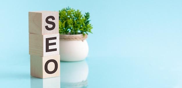 Seo-tekst op houten kubussen, op een blauwe achtergrond. op de achtergrond een groene plant in een witte pot. reflectie in een spiegelend oppervlak