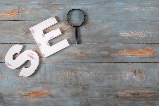 Seo-woord gevormd met witte letters en vergrootglas. zoekmachine optimalisatie concept.