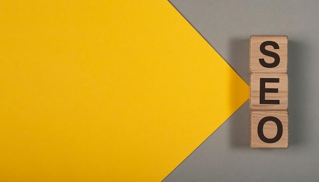 Seo woord over houten kubus dobbelstenen op gele achtergrond met kopie ruimte