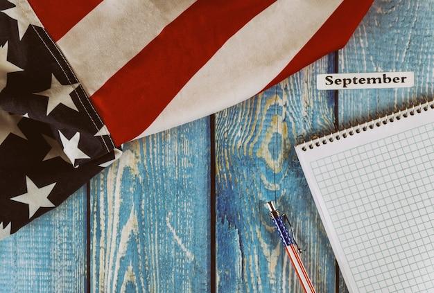 September-maand van kalenderjaar verenigde staten van amerika vlag van symbool van vrijheid en democratie met lege kladblok en pen op kantoor houten tafel