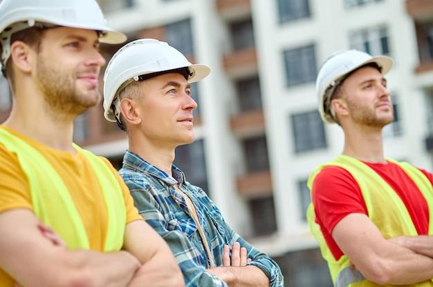 Serene aantrekkelijke grijsharige architect omringd door twee donkerharige jonge bouwers die met gevouwen armen in de verte staren