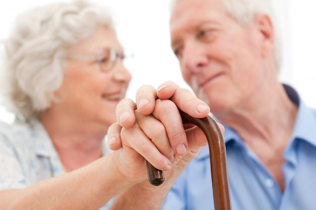 Serene bejaarde man en vrouw die elkaar steunen en bij elkaar blijven tijdens de oude dag