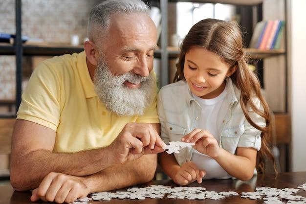 Serene familie. schattig pre-tiener meisje zit aan de tafel naast haar grootvader en samen met hem een puzzel in elkaar te zetten terwijl ze gelukkig lacht