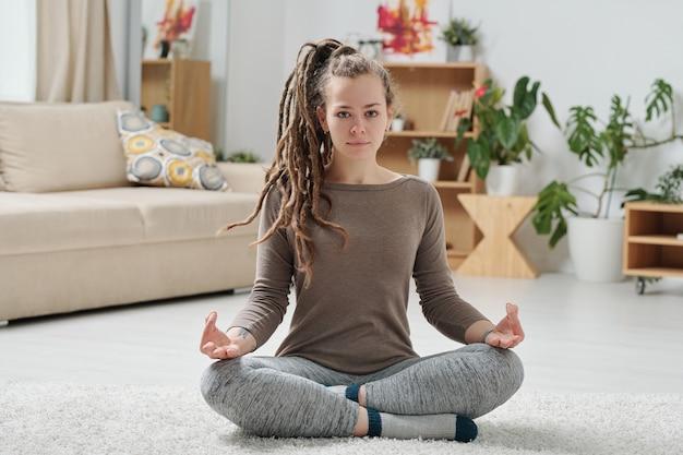 Serene meisje in activewear benen kruisen terwijl zittend op de vloer en het beoefenen van ontspannende yoga-oefening