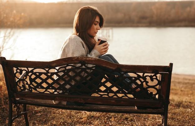 Serene vrouw met kopje afhaalkoffie in de buurt van meer