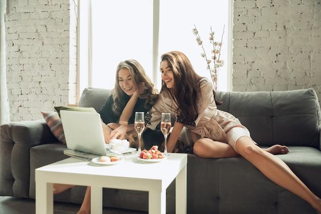 Serie kijken. blanke jonge meisjes, vrienden genieten van een weekend, klein vrijgezellenfeestje samen thuis. zie er mooi, blij, vrolijk uit. concept van vriendschap, wellness, levensstijl. oprechte emoties.
