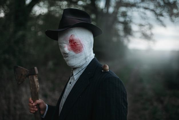Seriemaniak met bijl in het bos, gezicht gewikkeld in bebloede verbanden, bloedig moordenaarconcept, gekke moordenaar, misdaad en geweld horror