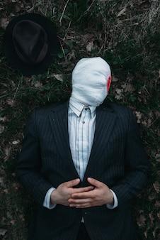 Seriemaniak met gezicht gewikkeld in bebloede verbanden ligt op de grond in het bos, gekke moordenaarconcept, psychomoordenaar