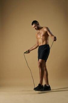 Serieus atleet met krachtige torso die een element van sportoefeningen binnenshuis doet